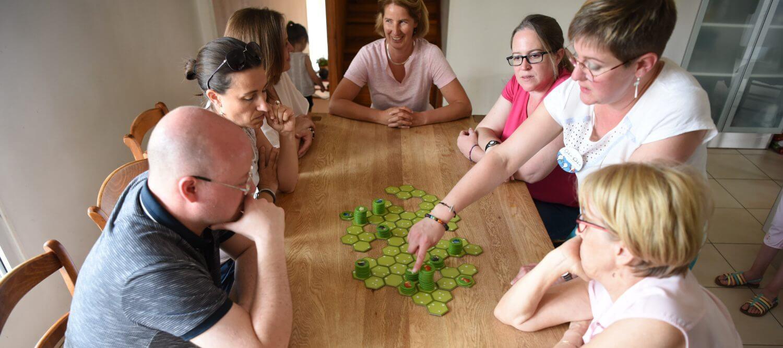 conseillère de vente à domicile expliquant un jeu de société à 6 adultes